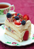 Berry Sponge Cake. Delicious slice of berry sponge cake with strawberries, blueberries and milk chocolate shavings with shallow depth of field stock images