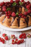 Berry sponge cake with chocolate icing on a plate close-up. vert Stock Image