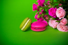 Berry spring color macaroons food background. Berry spring color macaroons food green  background with pink flowers Royalty Free Stock Photo