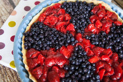 Berry tart with strawberries and blueberries. On wooden table and on fabric with color dots Stock Photography