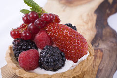 Berry Tart on Wood. Strawberry, raspberry, blackberry and redcurrant tart with cream on a wooden platter Royalty Free Stock Image