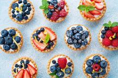 Berry tartlets background. Delicious summer pastry dessert top view. stock photo