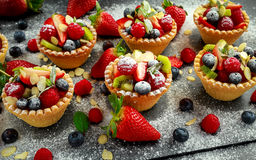 Berry tartlets with blueberries, raspberries, kiwi, strawberries, almond flakes in icing sugar. Royalty Free Stock Photography