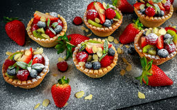 Berry tartlets with blueberries, raspberries, kiwi, strawberries, almond flakes in icing sugar. Stock Images