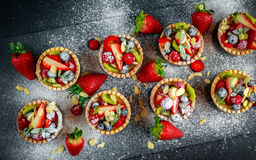 Berry tartlets with blueberries, raspberries, kiwi, strawberries, almond flakes in icing sugar. Royalty Free Stock Image