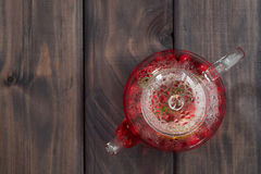 Berry tea in glass teapot on dark wooden table Royalty Free Stock Image