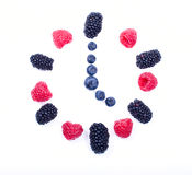 Berry watch five o'clock. Hours of raspberries, blackberries and blueberries on a white background. Five o'clock Stock Image