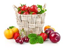 Berry in wicker basket still life. With fruits and green leaves, on white background Stock Photo
