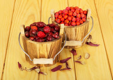 Berry wild rose, mountain ash in  bucket on light wood. Royalty Free Stock Images
