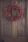Berry wreath. Fall berry wreath hanging on a wooden door Stock Photo