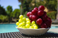 Berrys by the swimmimg pool. Grape in white plate on table by the swimming pool Royalty Free Stock Photography