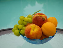 Berrys by the swimmimg pool. Peaches, grape and apricots in glass plate on table by the swimming pool Royalty Free Stock Image