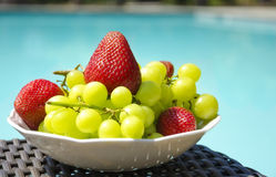 Berrys by the swimmimg pool. Strawberry and grape in white plate on table by the swimming pool Stock Photography