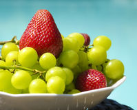 Berrys by the swimmimg pool. Strawberry and grape in white plate on the table by the swimming pool Stock Images