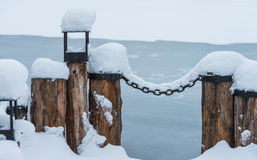 Berth with a chain in the snow Royalty Free Stock Photos