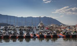 Berth with standing yachts and jet skis on a background of mountains royalty free stock photos