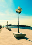 Berth with street-lamp on sea background Royalty Free Stock Photos