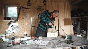 Beruf-, Leute-, Zimmerei-, Holzarbeit- und Leutekonzept - Tischler mit bohrender hölzerner Planke der elektrischen Bohrmaschine a stock footage