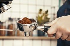 Berufs-barista reibt Kaffee an einer skandinavisch-ähnlichen Kaffeestube stockbilder