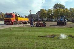 Berufsarbeitskräfte, die neue Grasrollen im Park mit speziellen Autos und Werkzeugen legen stockfotografie