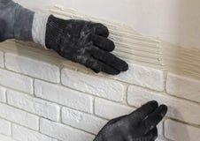 Berufsarbeitskraft, die eine Fliese auf Wand klebt Stockfoto