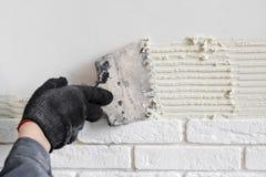 Berufsarbeitskraft, die eine Fliese auf Wand klebt Stockbild