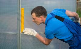 Berufsarbeitskraft, Kontrollen mithilfe eines Quadrats die Korrektheit der Installation des Gewächshauses, Polycarbonat Stockfoto
