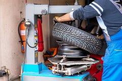 Berufsauto mechanisch in der Werkstatt, die Reifen ersetzt lizenzfreies stockfoto