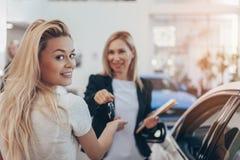 Berufsautohändler, der ihrem weiblichen Kunden hilft lizenzfreie stockfotografie