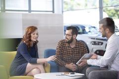 Berufsautohändler, der luxuriöse Fahrzeuge während des meeti anbietet lizenzfreies stockbild
