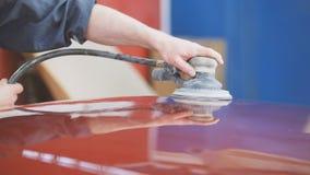 Berufsautoservice - eine Arbeitskraft poliert rotes Automobil stockbilder