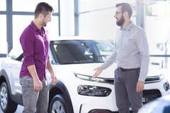 Berufsautoverkäufer, der herein exklusives Fahrzeug Käufer darstellt lizenzfreie stockfotos