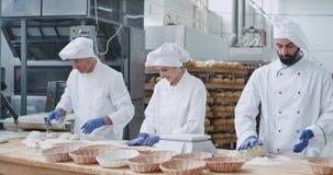Berufsbäcker, die Stücke Teig zu backendem Brot auf einer großen Tabelle in der Handelsküchenindustrie bilden stock video footage