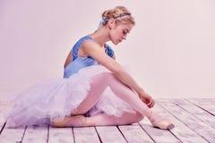 Berufsballerina, die auf ihre Ballettschuhe sich setzt lizenzfreie stockfotografie