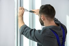 Berufsbauarbeiter, der Fenster installiert stockbilder