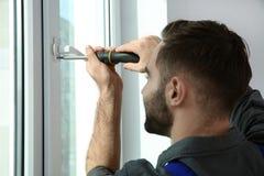 Berufsbauarbeiter, der Fenster installiert lizenzfreies stockfoto