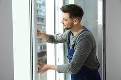 Berufsbauarbeiter, der Fenster installiert lizenzfreie stockfotos