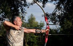 Berufsbogenschütze, der mit Bogen und Pfeil zielt Lizenzfreie Stockfotos