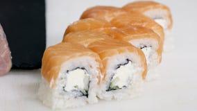 Berufschef, der asiatisches Lebensmittel und Sushi in der Restaurantküche kocht, bearbeitet und zubereitet Lizenzfreies Stockbild