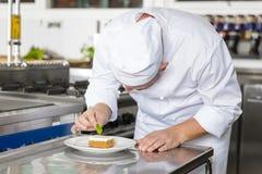 Berufschef verzieren Nachtischkuchen mit Zitronenblatt Lizenzfreies Stockbild