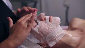 Berufscosmetologist, der ihre Hände auf Frau ` s Gesicht beim Apllying spezielle Maske auf weiblichem Kunde ` s Gesicht hält und stock video