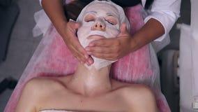 Berufscosmetologist, der ihre Hände auf Frau ` s Gesicht beim Apllying spezielle Maske auf weiblichem Kunde ` s Gesicht hält und stock footage