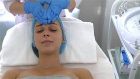 Berufscosmetologist und Dermatologe, die Gesichtsmassage eine junge Frau antut Verfahren für das Festziehen und das Verjüngen stock video