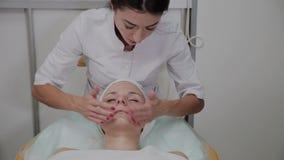 Berufscosmetologist wendet Feuchtigkeitscreme am Mädchengesicht an stock video footage