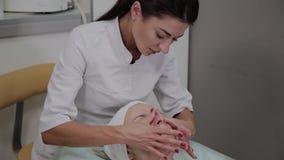 Berufscosmetologist wendet Feuchtigkeitscreme am Mädchengesicht an stock video