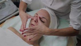 Berufscosmetologist wendet Feuchtigkeitscreme am Mädchengesicht an stock footage