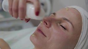 Berufscosmetologist wendet Feuchtigkeitscreme an, um gegenüberzustellen stock video footage
