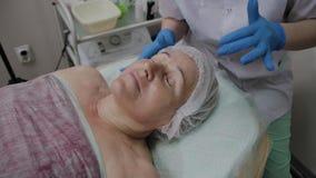 Berufscosmetologist wendet Feuchtigkeitscreme an, um gegenüberzustellen stock video