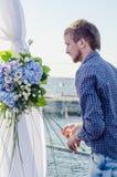 Berufsflorist bei der Arbeit: junger hübscher Mann, der Mode modernen Zusammensetzungsblumenstrauß von Blauem und von Weiß unters Lizenzfreies Stockbild