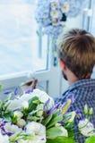 Berufsflorist bei der Arbeit: junger hübscher Mann, der Mode modernen Zusammensetzungsblumenstrauß von Blauem und von Weiß unters Lizenzfreie Stockbilder